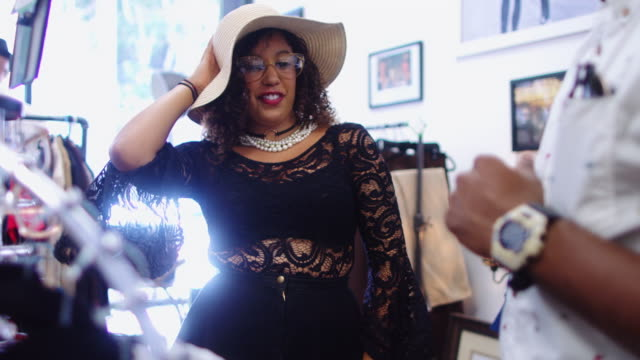Woman Trying on Hat, Glasses and Necklace in Vintage Store video