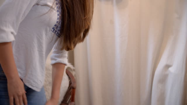 Woman trying on jeans in boutique changing room, mid section video
