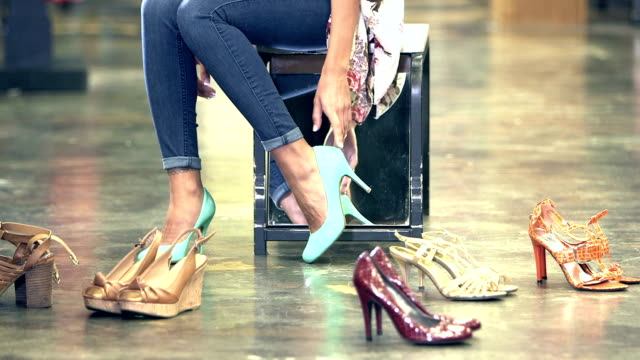 Woman trying on shoes in store Cropped view of a mixed race young woman trying on high heel shoes in a clothing store. shoe stock videos & royalty-free footage