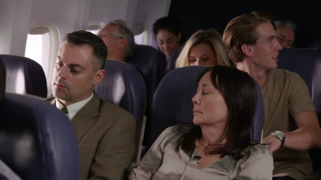 Woman trying to sleep on airplane flight Woman trying to sleep on airplane flight seat stock videos & royalty-free footage