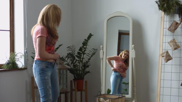 kvinna som försöker klämma in par gamla jeans - jeans bildbanksvideor och videomaterial från bakom kulisserna