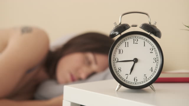 Woman turning alarm clock off in the morning