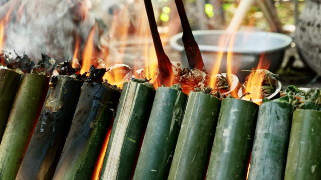 woman turning bamboo cakes cooking on fire - ugnsstekt bildbanksvideor och videomaterial från bakom kulisserna