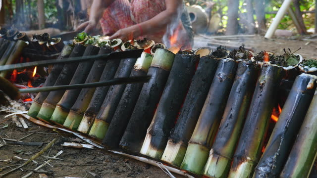 Woman turning bamboo cakes cooking on fire video