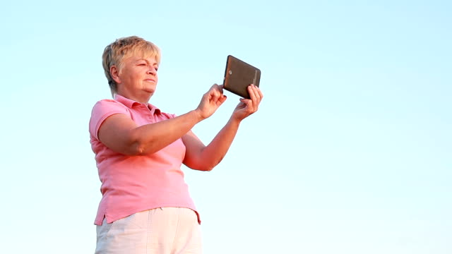 woman turns on a tablet on a sky background video