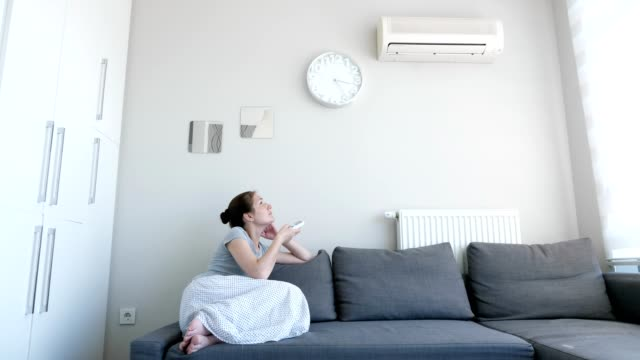 vídeos de stock, filmes e b-roll de a mulher gira sobre o condicionador de ar do controlo a distância que senta-se no sofá. - ar condicionado