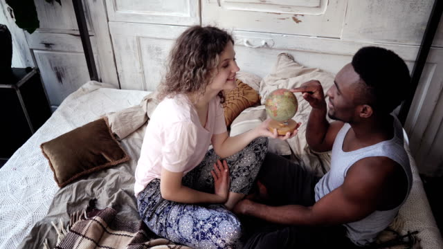 Woman twists the globe, man picks the location to traveling. Multiracial couple in pajamas rejoice, hug and kiss video