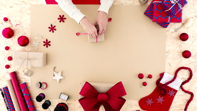 Woman tying a ribbon Woman tying a ribbon around Christmas present wrapped stock videos & royalty-free footage