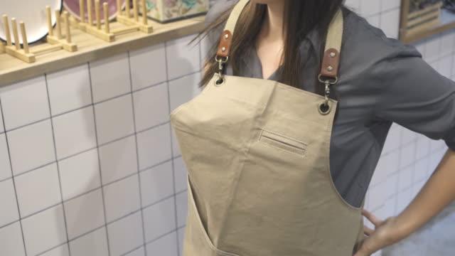 vídeos de stock e filmes b-roll de woman tying an apron for working - avental