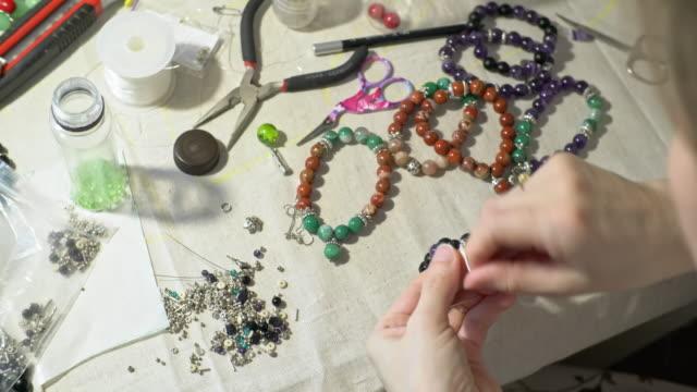 vidéos et rushes de femme liant fini bracelet fait main - joaillerie