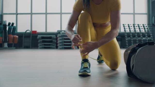 frau bindet ihre trainingsschuhe - gewichtstraining stock-videos und b-roll-filmmaterial