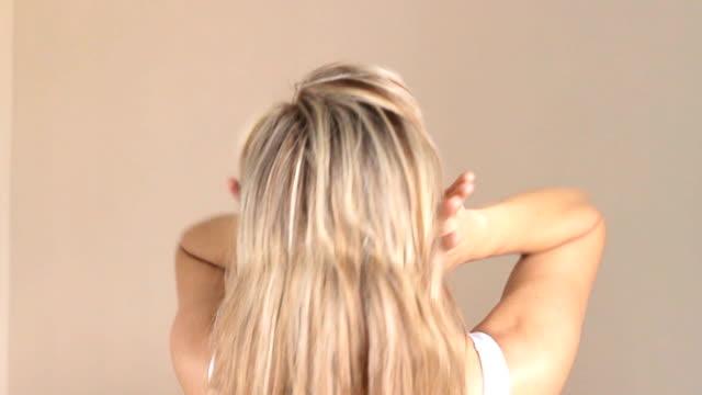 stockvideo's en b-roll-footage met vrouw koppelverkoop haar lange glad haar in paardenstaart, het maken van kapsel, terug te bekijken. haarverzorging concept. - paardenstaart haar naar achteren