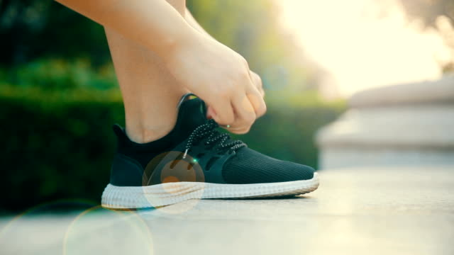 vídeos y material grabado en eventos de stock de atar su zapato deportivo mujer - amarrado