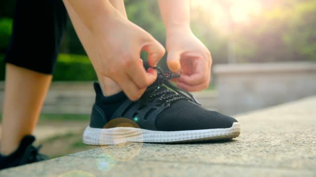donna che lega la sua scarpa sportiva - annodare video stock e b–roll