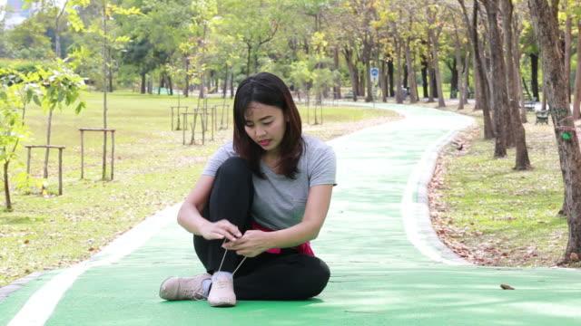 woman tying shoelace in running shoe during jogging video