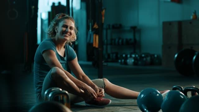 女性は靴ひもを結ぶと座って - 耐久力点の映像素材/bロール