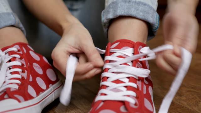 donna che lega i lacci delle scarpe da scarpe da scarpe da scarpe da sole rosse sedute su un pavimento. primo piano sulle mani ragazza legare lacci pronti per lo sport, strada a piedi. - annodare video stock e b–roll
