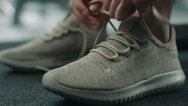 donna legare lacci delle scarpe da ginnastica - annodare video stock e b–roll