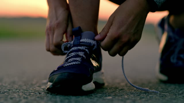 SLO MO Woman tying shoelaces on running shoes Slow motion close up shot of an unrecognizable woman tying shoelaces before start jogging somewhere in the country. shoe stock videos & royalty-free footage