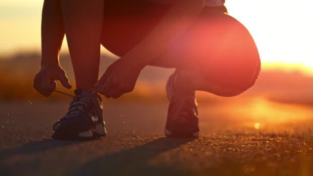 slo mo 女性ランニング シューズの靴ひもを結ぶ - 結ぶ点の映像素材/bロール