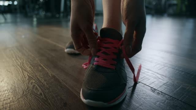 stockvideo's en b-roll-footage met vrouw koppelverkoop schoenveters - running shoes