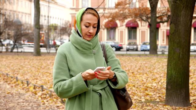 vidéos et rushes de message de texte de type de femme sur un téléphone intelligent, regardez montre-bracelet, prendre rendez-vous - étudiant(e)
