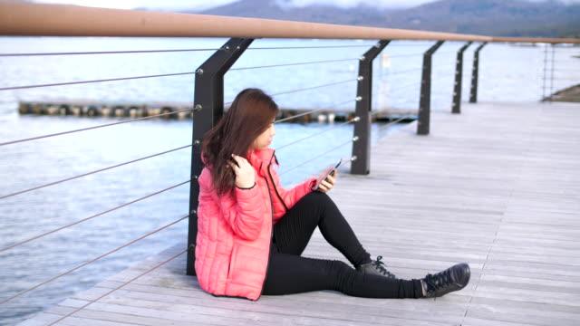 vídeos y material grabado en eventos de stock de tipos de mujer un mensaje en su teléfono - nieve amontonada