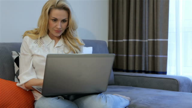 Woman types on laptop at home video