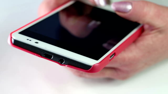 Woman types sms on her mobile phone. Close up of woman hands with red smartphone video