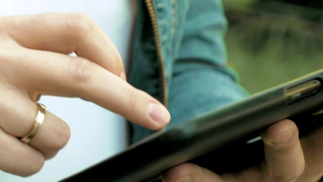 Woman types texts on tablet pc walking outdoors video