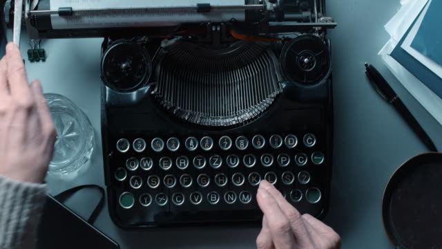 LD POV Woman typing a letter on old typewriter. Locked down high angle point of view shot of a woman typing a letter on an old typewriter with a glass of water and a notebook by her side on the table. typewriter stock videos & royalty-free footage