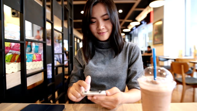 Woman typing a smart phone at coffee shop video
