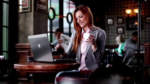 vídeos de stock e filmes b-roll de mulher escrevendo no laptop e beber café. - coffe shop