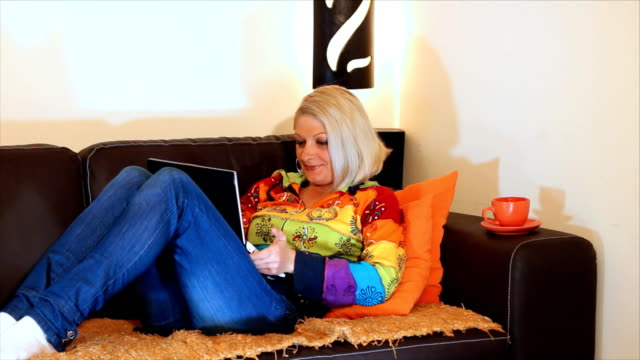 Woman typing on a laptop computer HD 1080: Beautiful woman lying and using laptop computer. Light of the bedside lamp, a beautiful home environment portrays the warmth of home. blue hair stock videos & royalty-free footage