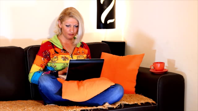 Woman typing on a laptop computer HD 1080: Beautiful woman sit and using laptop computer with coffee or tea. Light of the bedside lamp, a beautiful home environment portrays the warmth of home. blue hair stock videos & royalty-free footage