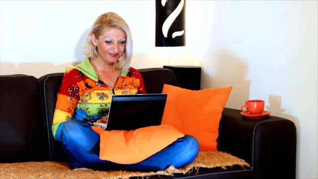 Woman typing on a laptop computer HD 1080: Beautiful woman sit and using laptop computer, with coffee or tea. Light of the bedside lamp, a beautiful home environment portrays the warmth of home. blue hair stock videos & royalty-free footage