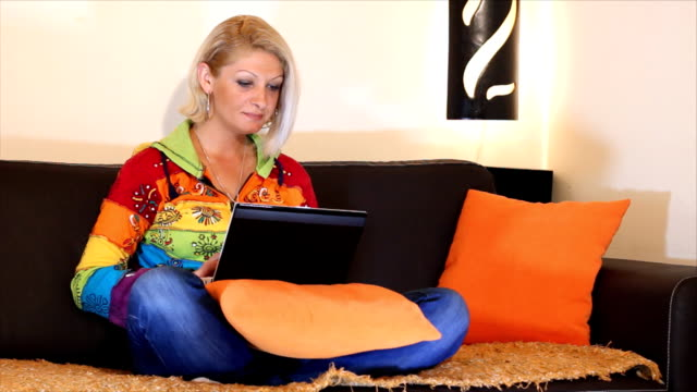 Woman typing on a laptop computer HD 1080: Beautiful woman sit and using laptop computer. Light of the bedside lamp, a beautiful home environment portrays the warmth of home. blue hair stock videos & royalty-free footage