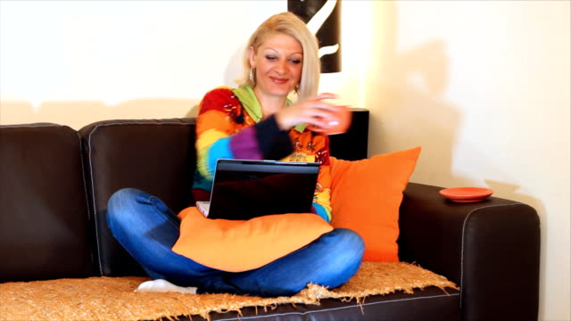 Woman typing on a laptop computer HD 1080: Beautiful woman sit and using laptop computer, drink coffee or tea. Light of the bedside lamp, a beautiful home environment portrays the warmth of home. blue hair stock videos & royalty-free footage