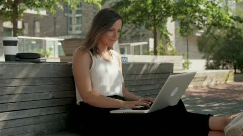stockvideo's en b-roll-footage met vrouw typen op een laptop - buitenopname