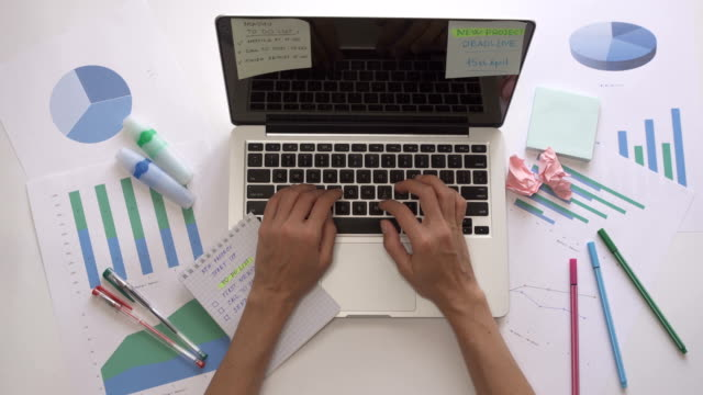 woman typing on computer and put ticks in to do list in notebook. - to do list video stock e b–roll
