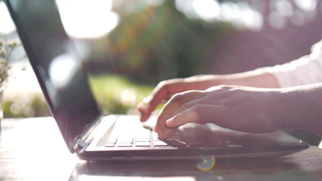 slow motion : donna che digita sulla tastiera del laptop, lavorare a casa, dolly girato - ambientazione esterna video stock e b–roll