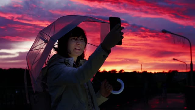 Woman under umbrella makes selfie on smarthone at dusk with pink-blue clouds. video