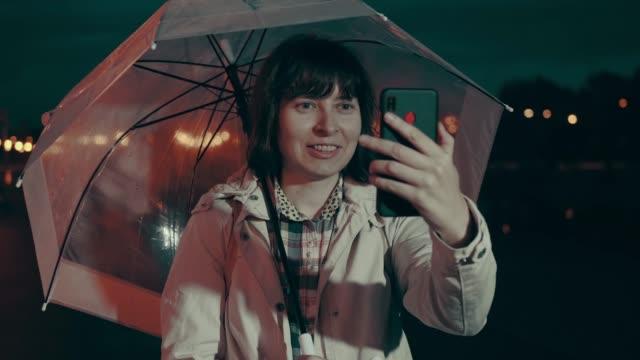 Woman under umbrella makes selfie on smarthone at night. video