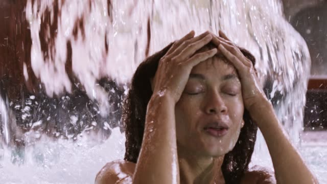 woman under waterfall at spa - sotto video stock e b–roll