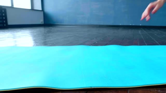 una donna dispiega un tappeto per praticare yoga in studio. - materassino ginnico video stock e b–roll