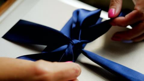 vidéos et rushes de femme libère un arc bleu - cadeau