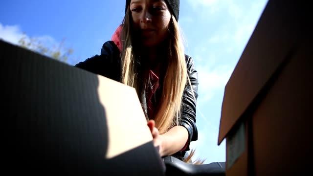 stockvideo's en b-roll-footage met vrouw lossen kartonnen dozen uit auto kofferbak - boomstam