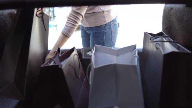 Woman unloads groceries in bags into her car