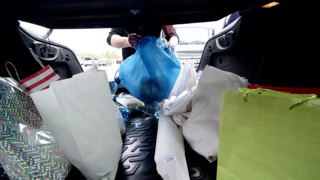 stockvideo's en b-roll-footage met woman unloads groceries in bags into her car - boodschappentas tas