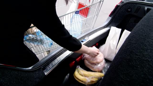 Femme unloads provisions en plastique et sacs en papier en short - Vidéo